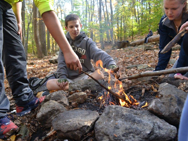 A group of campers poking at a campfire with sticks.