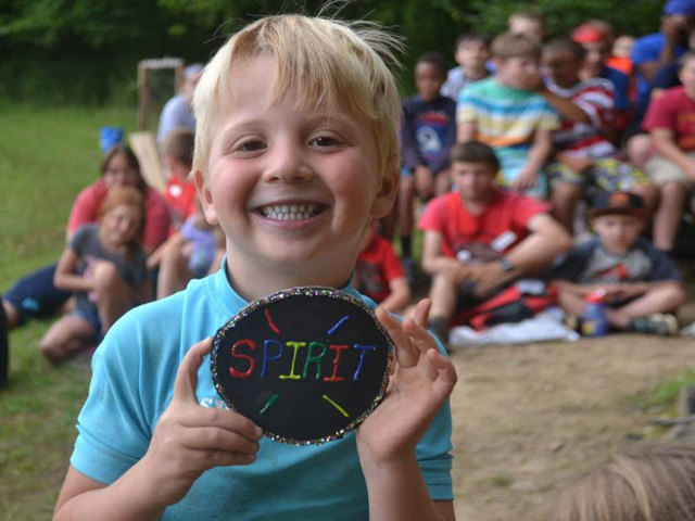 A boy smiling and holding a decorated board that says