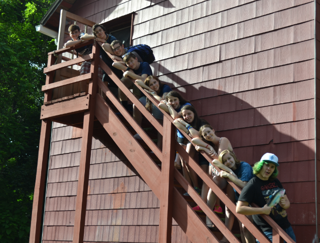 Camp counselors posing on a staircase outdoors.