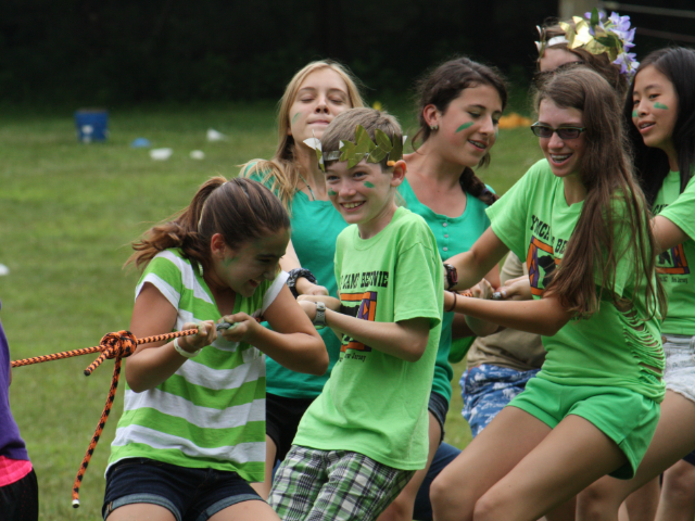 A group of kids in green shirts playing tug of war.