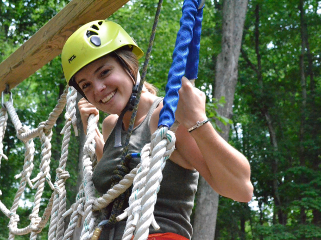 Girl in a bright green hat on a ropes course.