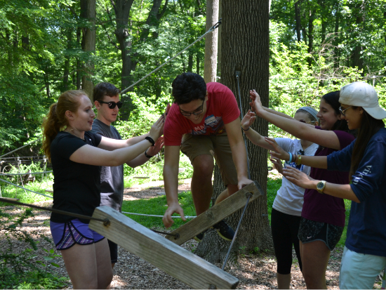 A group working together to help one person balance on a rope.